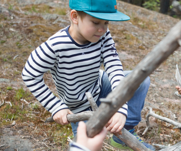 Boy playing with wood 600 x 500