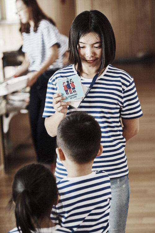 Teacher with HEI Pictogram in hand   Source: HEI Schools